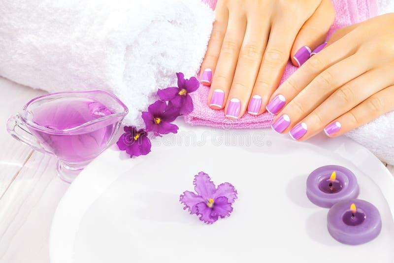 Fransk manikyr med violetta blommor Spa royaltyfria foton