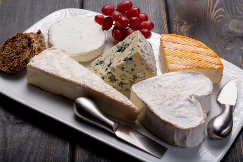 Fransk ostplatta i sortimentet, ädelost, brie, munster, fotografering för bildbyråer