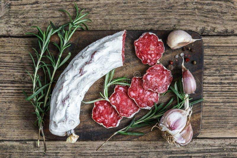 Fransk salami med rosmarin, vitlök och pepparkorn på träskärbräda över lantlig bakgrund Top beskådar arkivbilder