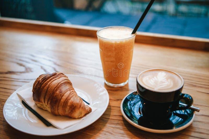 Fransk traditionell giffelefterrätt bredvid kaffecappuccino och orange fruktsaft i ett kafé för frukost arkivbild