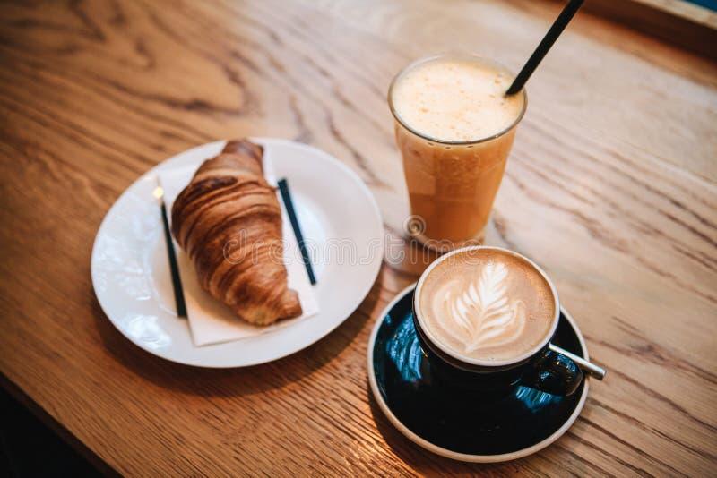 Fransk traditionell giffelefterrätt bredvid kaffecappuccino och orange fruktsaft i ett kafé för frukost royaltyfri foto