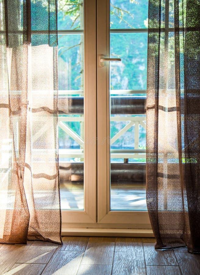 Franska dörrar öppnar på en balkong med en sikt av lövrika gröna träd Natur begreppet kopplar av kall royaltyfri fotografi