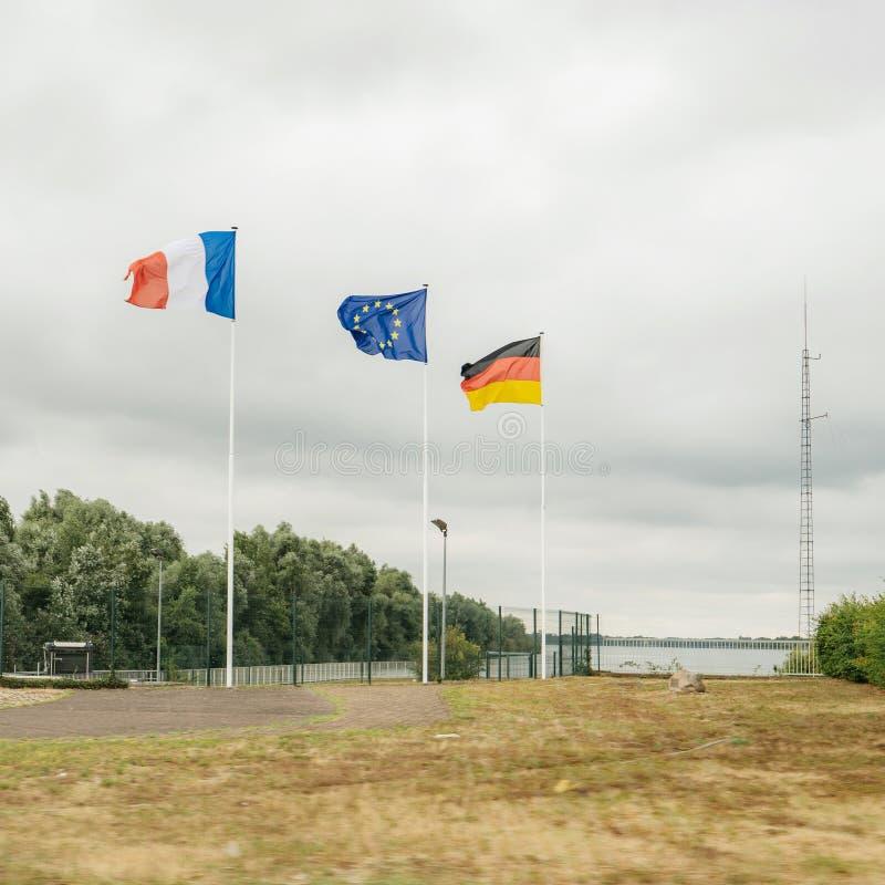 Franska, europeiska och tyska flaggor som viftar nära gränsen arkivfoton