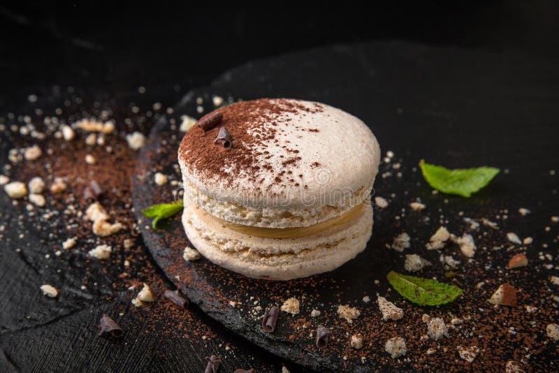 Franska färgrika macarons på svart bakgrund royaltyfri foto