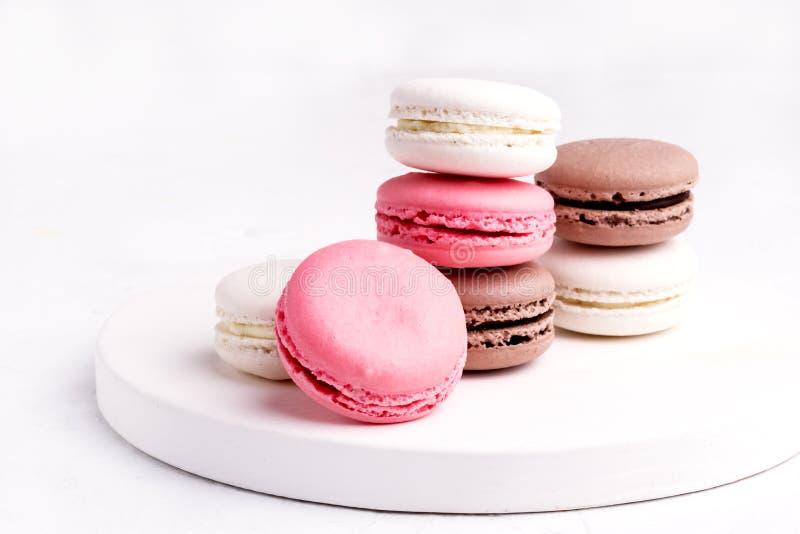 Franska färgrika Macarons färgrika pastellfärgade Macarons på vit bakgrundsWhitr rosa färger och brunt Macaron royaltyfria bilder