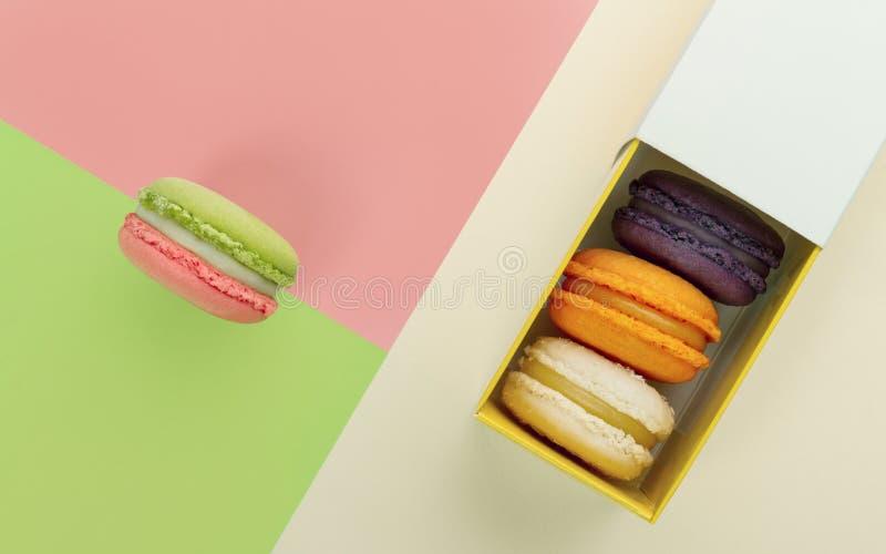Franska macarons boxas på gräsplan och rosa bakgrund för geometrisk design royaltyfri bild