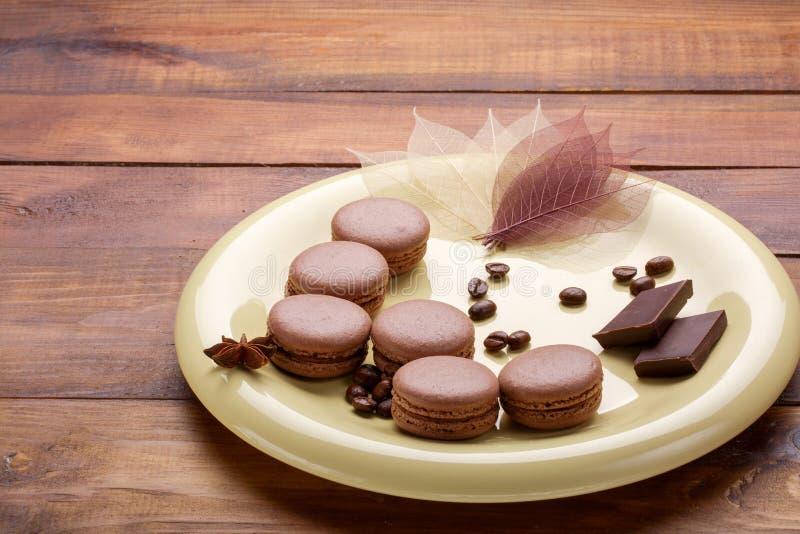 Franska makron med kaffebönor och choklad på en platta royaltyfri fotografi