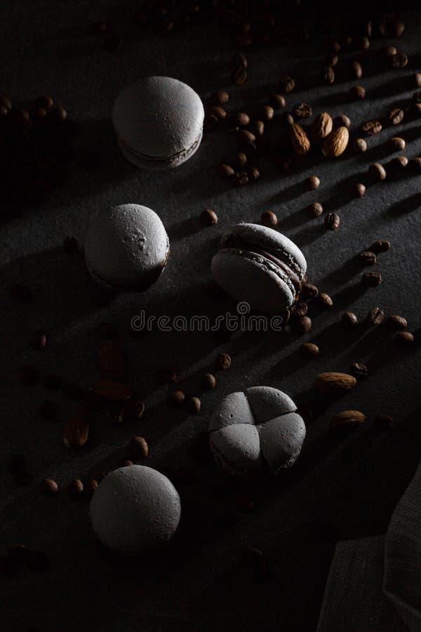 Franska makron som isoleras med kaffebönor Selektivt fokusera makron i mörk sida H?rliga makron stilfullt arkivfoto