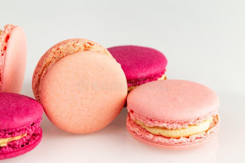 Franska rosa och magentafärgade macarons eller makron, closeup, bästa sikt för sida på en vit bakgrund arkivbilder