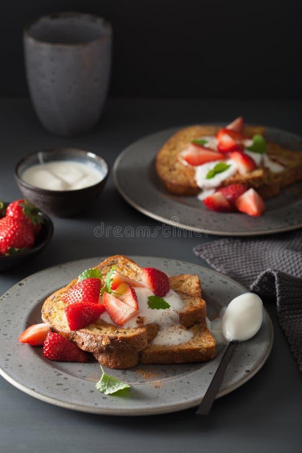Franska rostade bröd med yoghurt och jordgubbar för frukost arkivbild