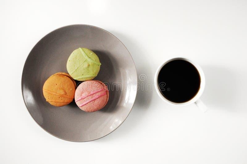 Franskakakamakron på plattan med kaffe Färgrika smakliga kakamacarons Morgonfrukost royaltyfri bild