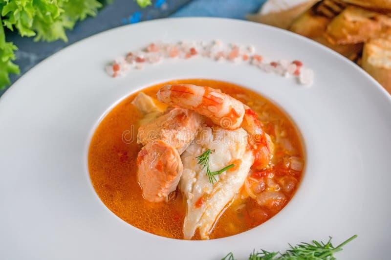 Franskan fiskar soppabouillabaissen med skaldjur, laxfilén, räka, rich anstrykning, läcker matställe i en härlig vit royaltyfri foto