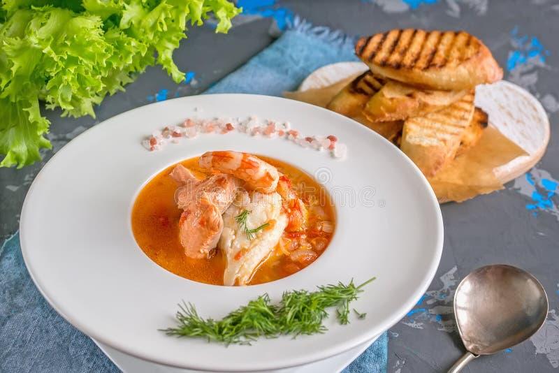 Franskan fiskar soppabouillabaissen med skaldjur, laxfilén, räka, rich anstrykning, läcker matställe i en härlig vit arkivfoton