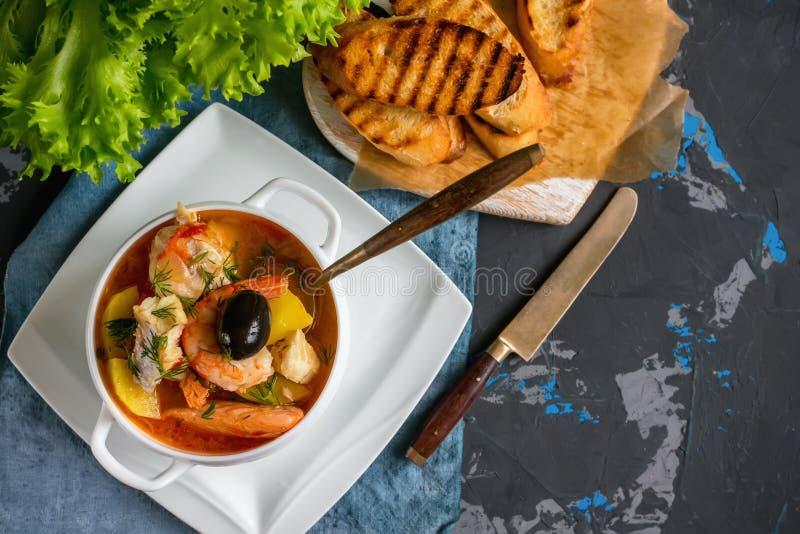 Franskan fiskar soppabouillabaissen med skaldjur, laxfilén, räka, rich anstrykning, läcker matställe i en vit härlig platta kopia arkivbild