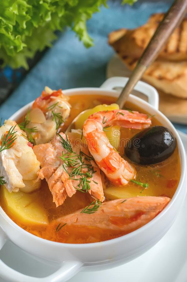 Franskan fiskar soppabouillabaissen med skaldjur, laxfilén, räka, rich smakar, den läckra matställen i en vit härlig platta arkivfoton