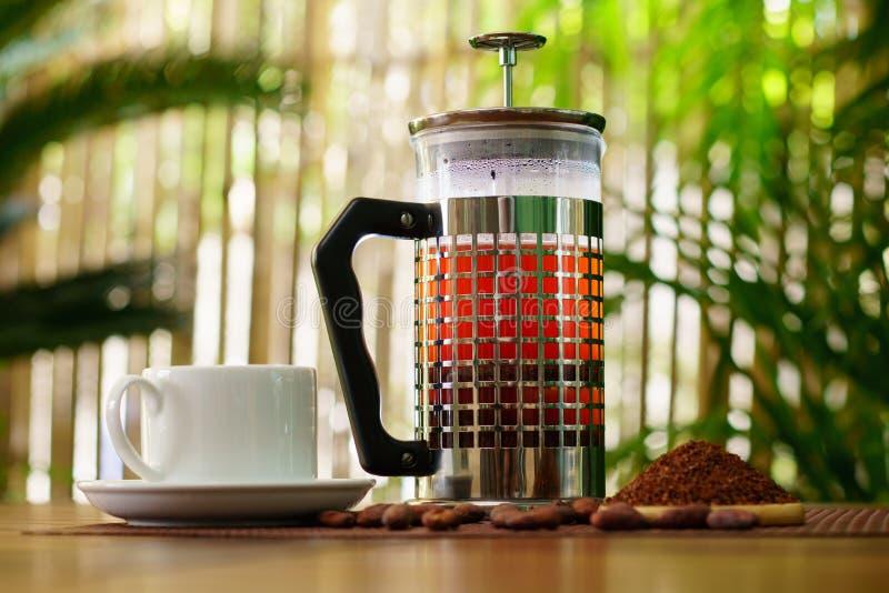 Franskan trycker på bryggade kakaostift och den vita koppen av kakao på trätabellen arkivfoton