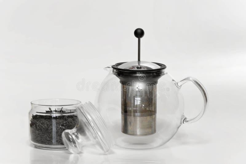 Franskan trycker på den glass brygga tekannan och den glass behållaren med svart te fotografering för bildbyråer