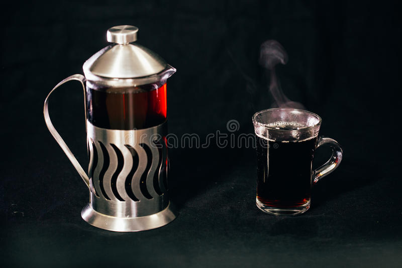 Franskan trycker på med te och en genomskinlig kopp te på en svart bakgrund arkivbild