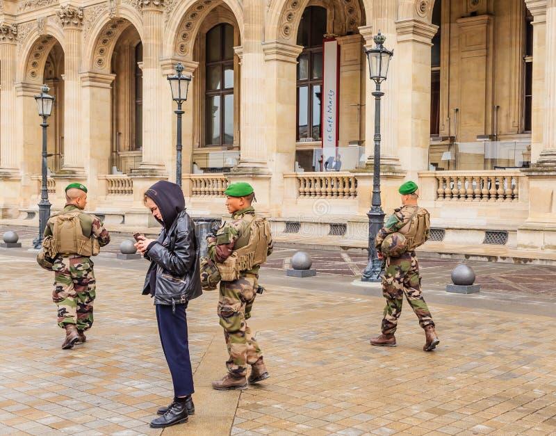 Franskasoldater som patrullerar nära Louvremuseum paris arkivbild
