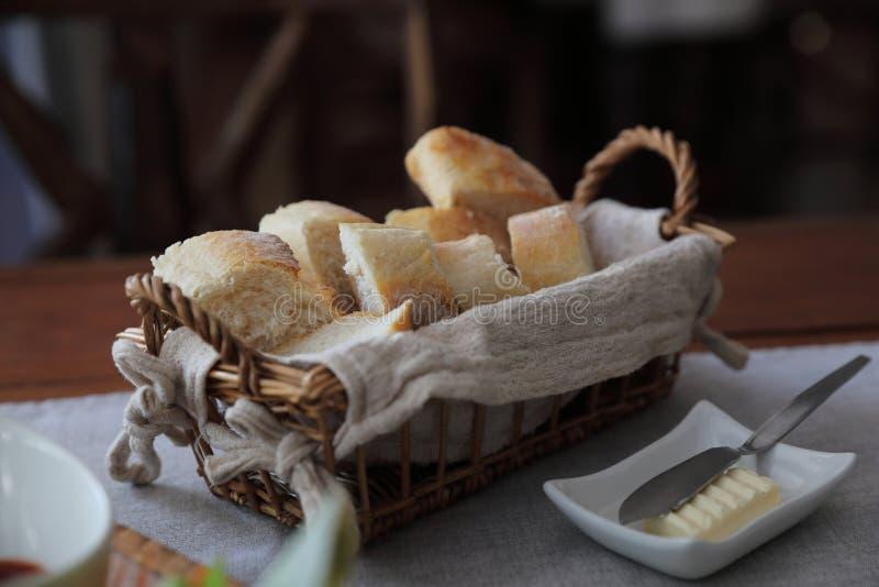 Franskbrödbagetter i träkorg träbakgrunden arkivfoto