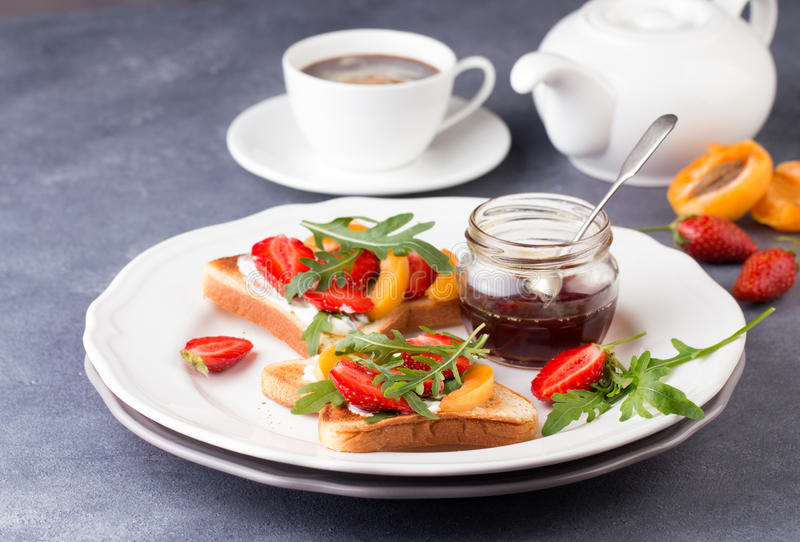 Franskt rostat bröd med nya jordgubbar och persikor royaltyfri foto
