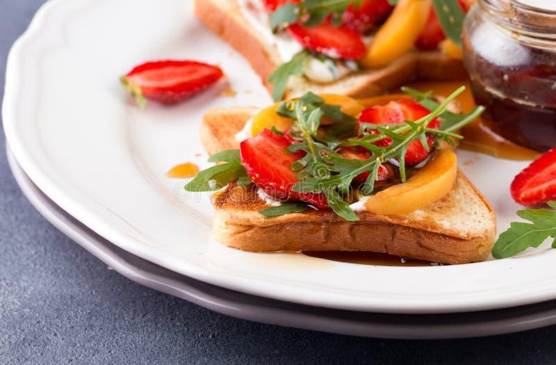 Franskt rostat bröd med nya jordgubbar och persikor arkivbilder