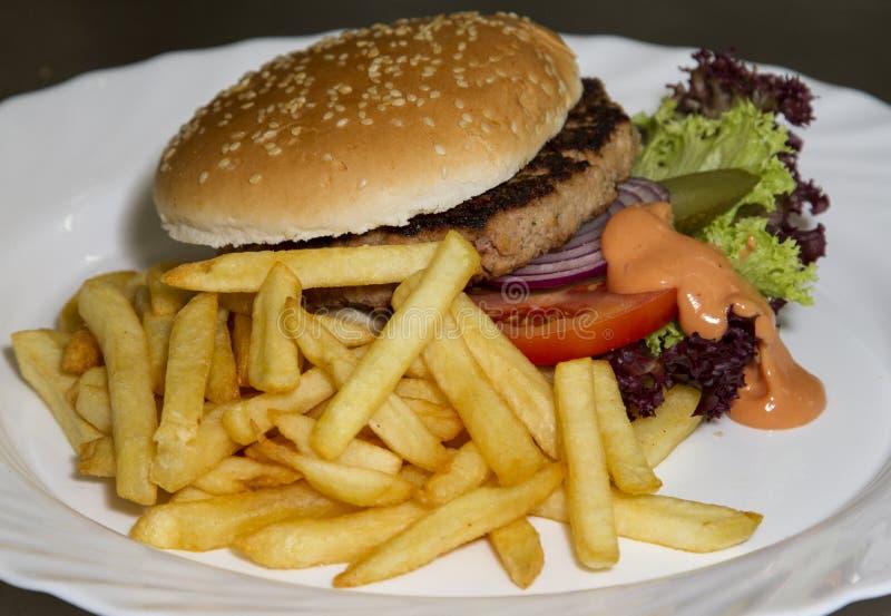 fransmannen steker hamburgaren arkivbild