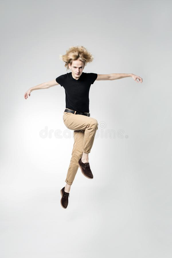 A frantic and expressive jump, hair scatter in different directions. Portrait of a jumping man stock image