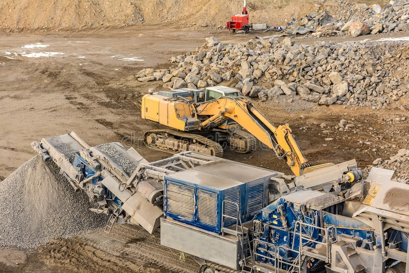 Frantoio per pietre ed escavatore in una miniera a cielo aperto immagine stock libera da diritti