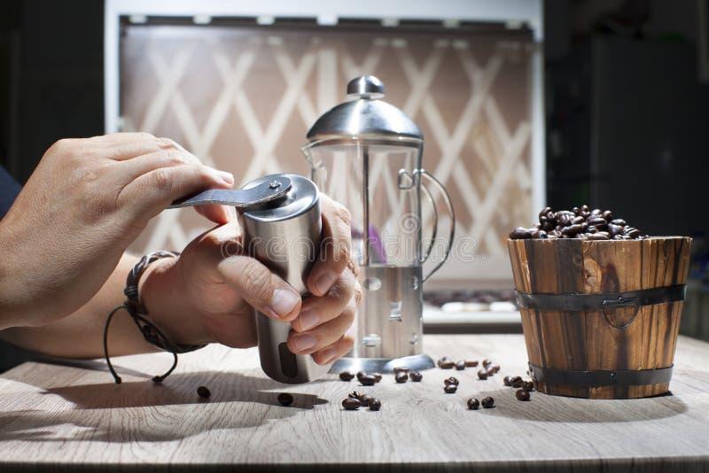 Frantumi i chicchi di caffè arrostiti Frantumazione con una smerigliatrice manuale del chicco di caffè della mano immagine stock