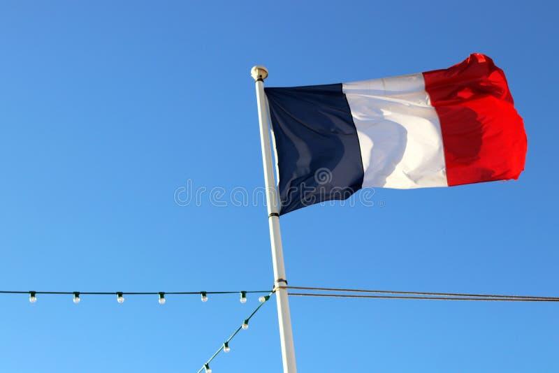 Französische Flagge Frankreichs mit einer tiefen Froschperspektive des blauen Himmels stockbilder