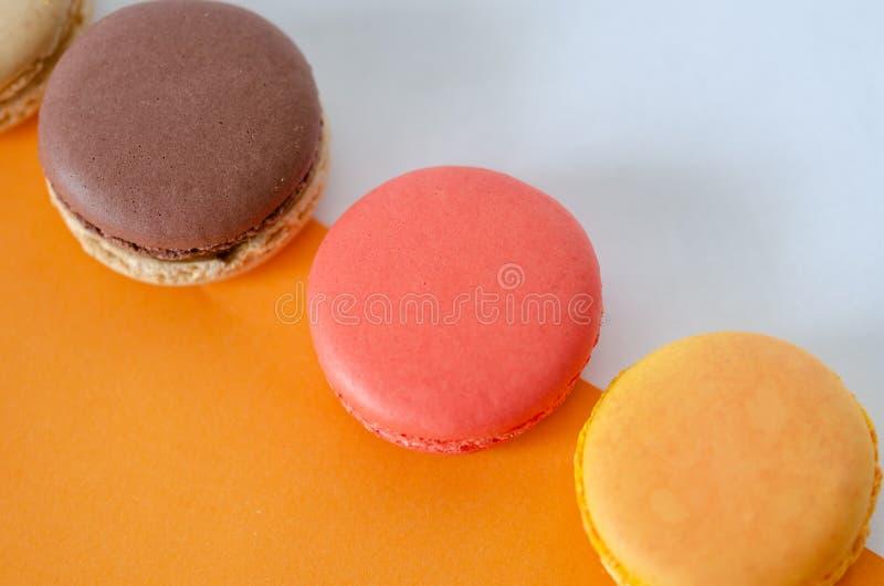 Französische macarons sind auf dem orange-weißen Hintergrund stockbilder