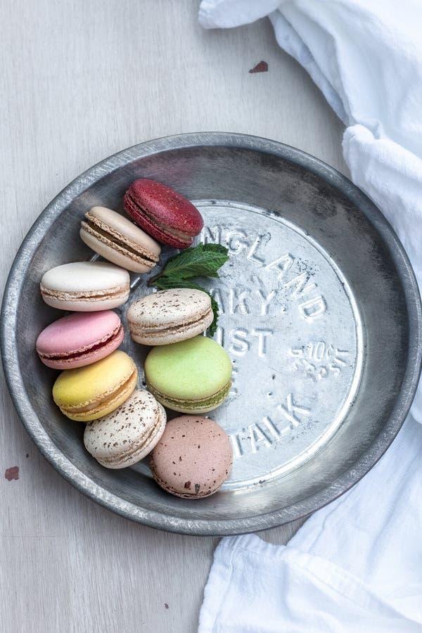 Französische macarons von verschiedenen Farben gedient auf einer metallischen silbernen Platte stockbilder