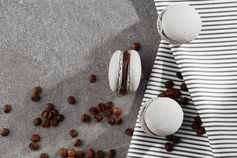 Französische Makronen auf gestreifter Serviette mit Kaffeebohnen Selektiver Fokus Makrone im grauen Ton Sch?n lizenzfreie stockfotografie