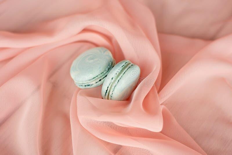 Französische Makronen des Kuchens, süße blaue Makronen auf einer Platte auf einem rosa Hintergrund stockfoto