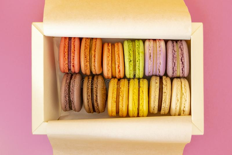 Französische Makronen des Kuchens, süße bunte macarons im weißen Kasten auf rosa Hintergrund stockfotos