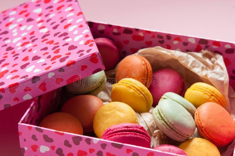 Französische Makronen in einem rosa Kasten mit Herzen stockbilder