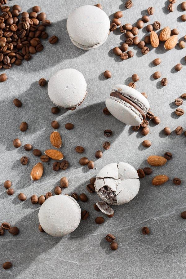 Französische Makronen lokalisiert mit Kaffeebohnen Selektiver Fokus Makrone im grauen Ton Französische Abbruch macarons auf graue stockfotografie