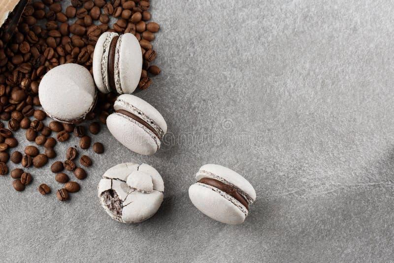 Französische Makronen lokalisiert mit Kaffeebohnen Selektiver Fokus Makrone im grauen Ton Französische Abbruch macarons auf graue lizenzfreie stockbilder