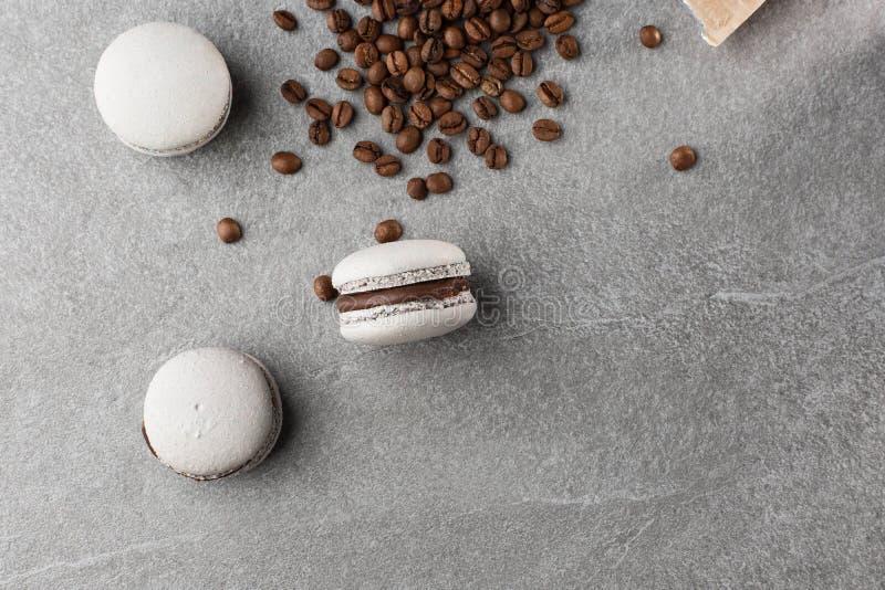 Französische Makronen lokalisiert mit Kaffeebohnen Selektiver Fokus Makrone im grauen Ton Drei schöne Makronen auf Grau lizenzfreies stockbild