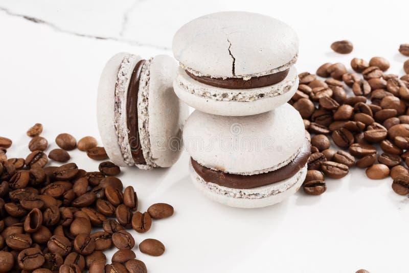 Französische Makronen lokalisiert mit Kaffeebohnen Selektiver Fokus Makrone im grauen Ton Schöne Makronen auf Marmor lizenzfreie stockbilder
