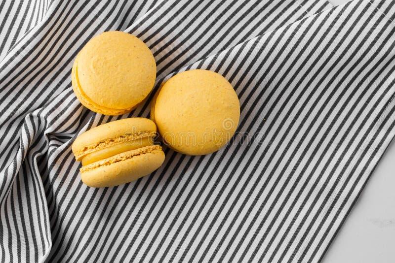 Französische Makronen lokalisierten Selektiver Fokus Schöne gelbe Makronen auf gestreiftem Serviettenhintergrund Stilvolle Anordn stockbild