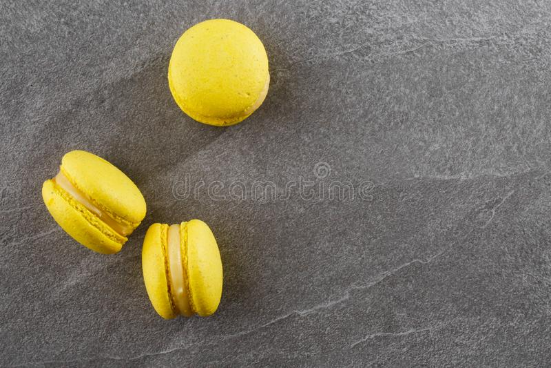 Französische Makronen lokalisierten Selektiver Fokus Schöne gelbe Makronen auf grauem Steinhintergrund Stilvolle Anordnung lizenzfreie stockfotografie