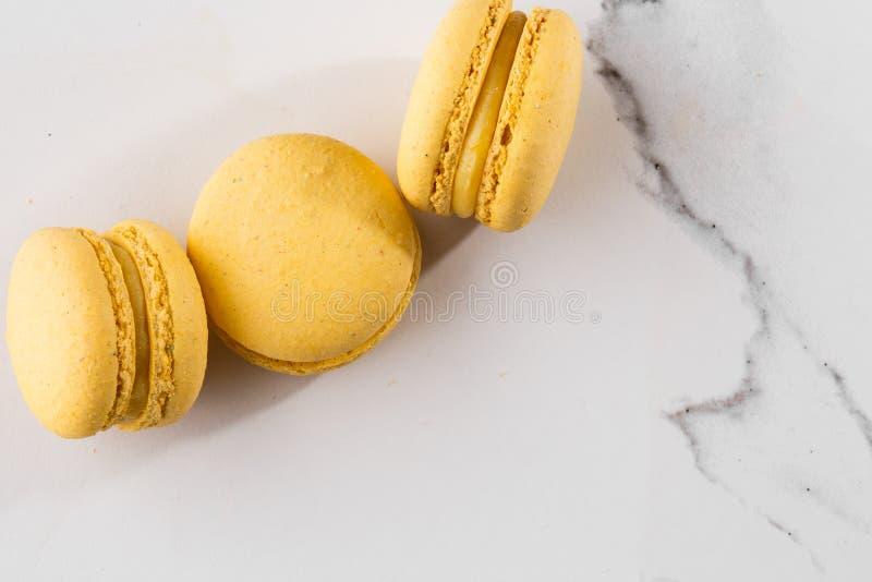 Französische Makronen lokalisierten Selektiver Fokus Schöne gelbe Makronen auf Marmorhintergrund Stilvoller Anordnungsbonbon stockfotografie