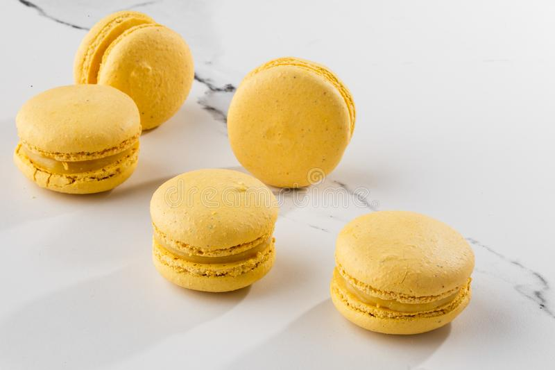 Französische Makronen lokalisierten Selektiver Fokus Schöne gelbe Makronen auf Marmorhintergrund Stilvoller Anordnungsbonbon stockbild