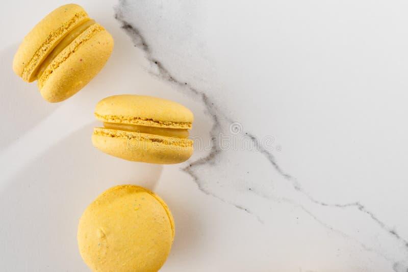 Französische Makronen lokalisierten Selektiver Fokus Schöne gelbe Makronen auf Marmorhintergrund Stilvoller Anordnungsbonbon lizenzfreie stockfotografie