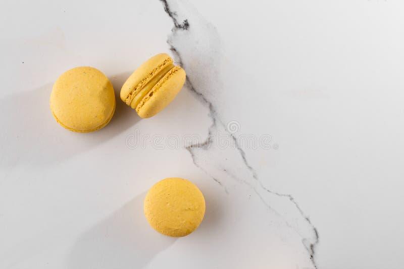 Französische Makronen lokalisierten Selektiver Fokus Schöne gelbe Makronen auf Marmorhintergrund Stilvoller Anordnungsbonbon lizenzfreies stockbild