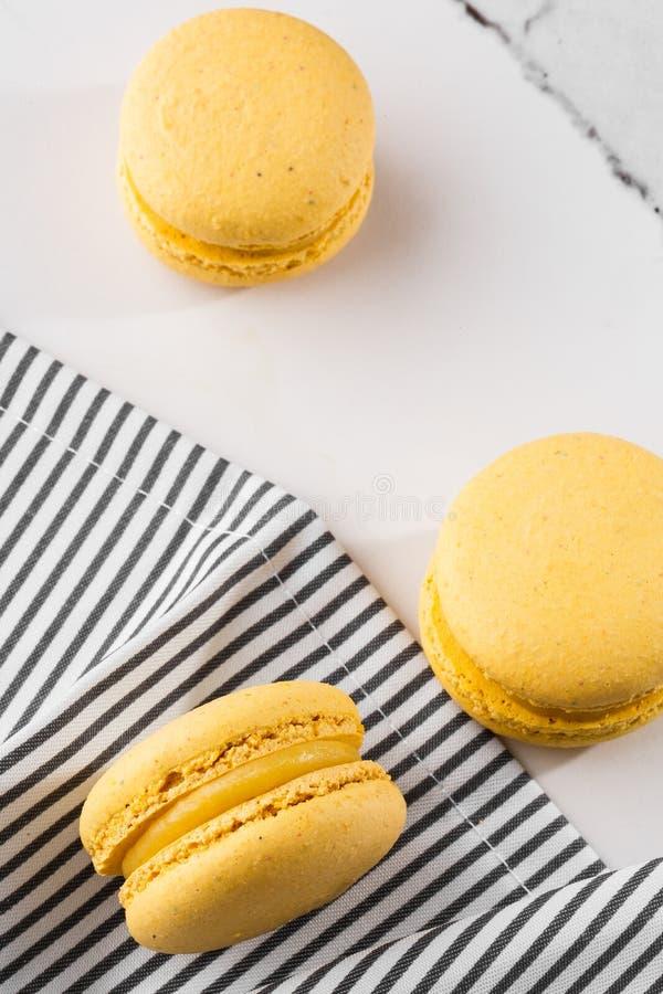 Französische Makronen lokalisierten Selektiver Fokus Schöne gelbe Makronen in gestreifter Serviette auf Marmorhintergrund stilvol stockbild