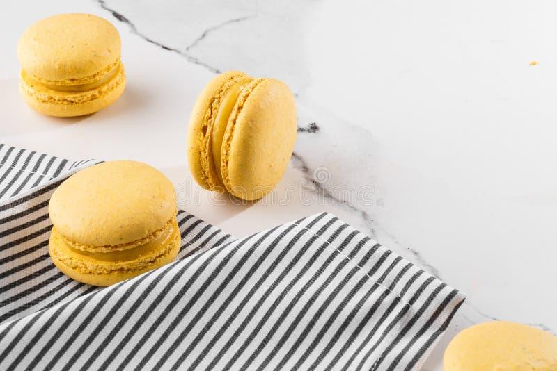 Französische Makronen lokalisierten Selektiver Fokus Schöne gelbe Makronen in gestreifter Serviette auf Marmorhintergrund stilvol lizenzfreies stockfoto