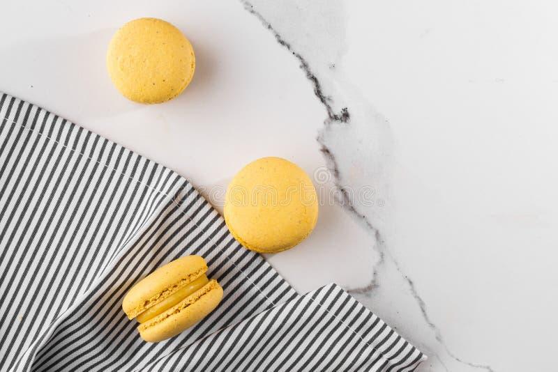 Französische Makronen lokalisierten Selektiver Fokus Schöne gelbe Makronen in gestreifter Serviette auf Marmorhintergrund stilvol stockbilder
